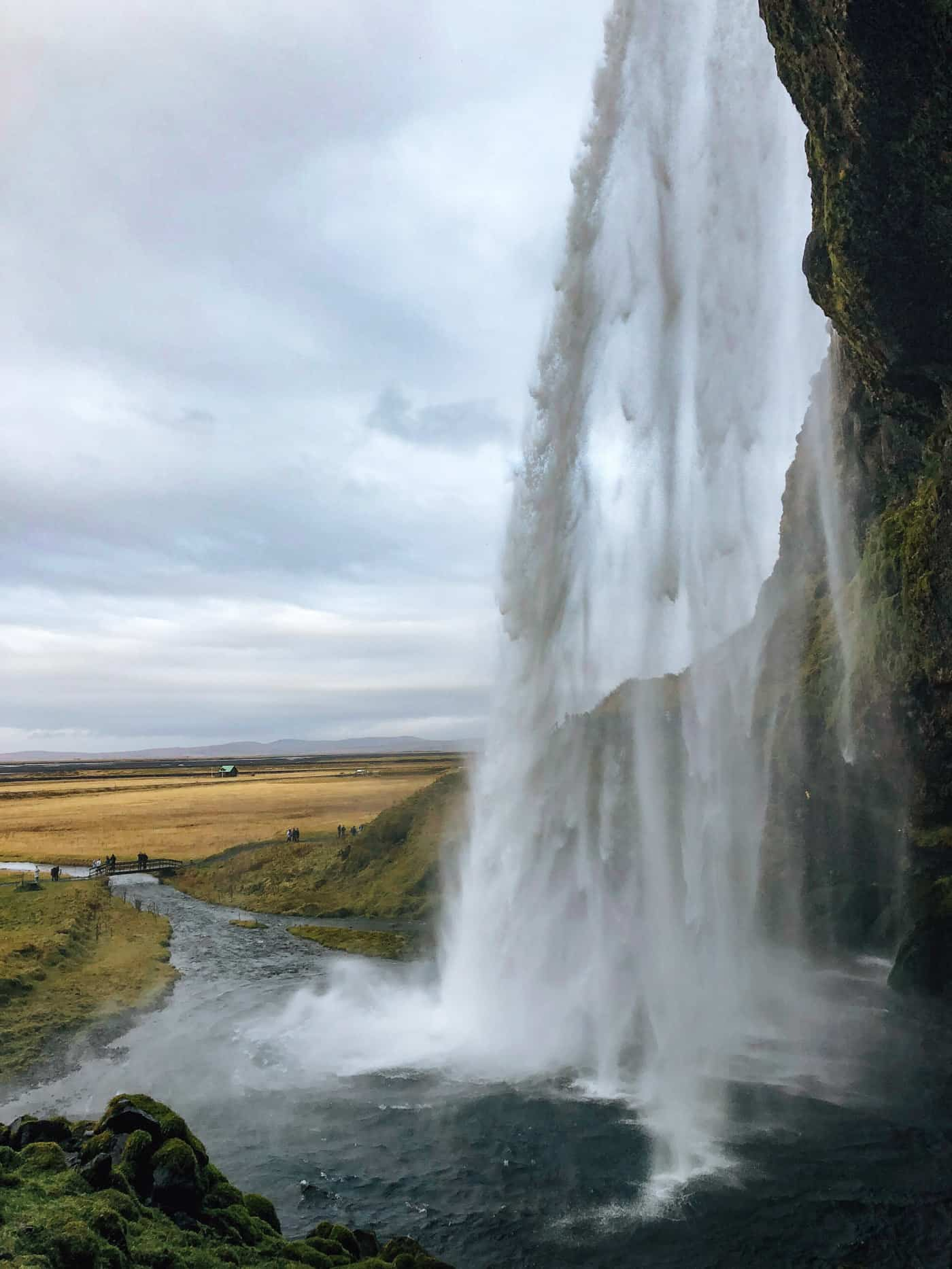 Walking behind Seljalandsfoss waterfall on the south coast of iceland